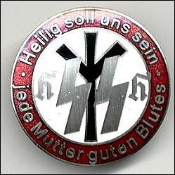 """Lebensborn-Abzeichen: """"Heilig soll uns sein jede Mutter guten Blutes"""", im Kreis die Lebensrune, das SS-Zeichen und die Initialen HH für Heinrich Himmler, Reichsführer SS und Chef der Polizei"""